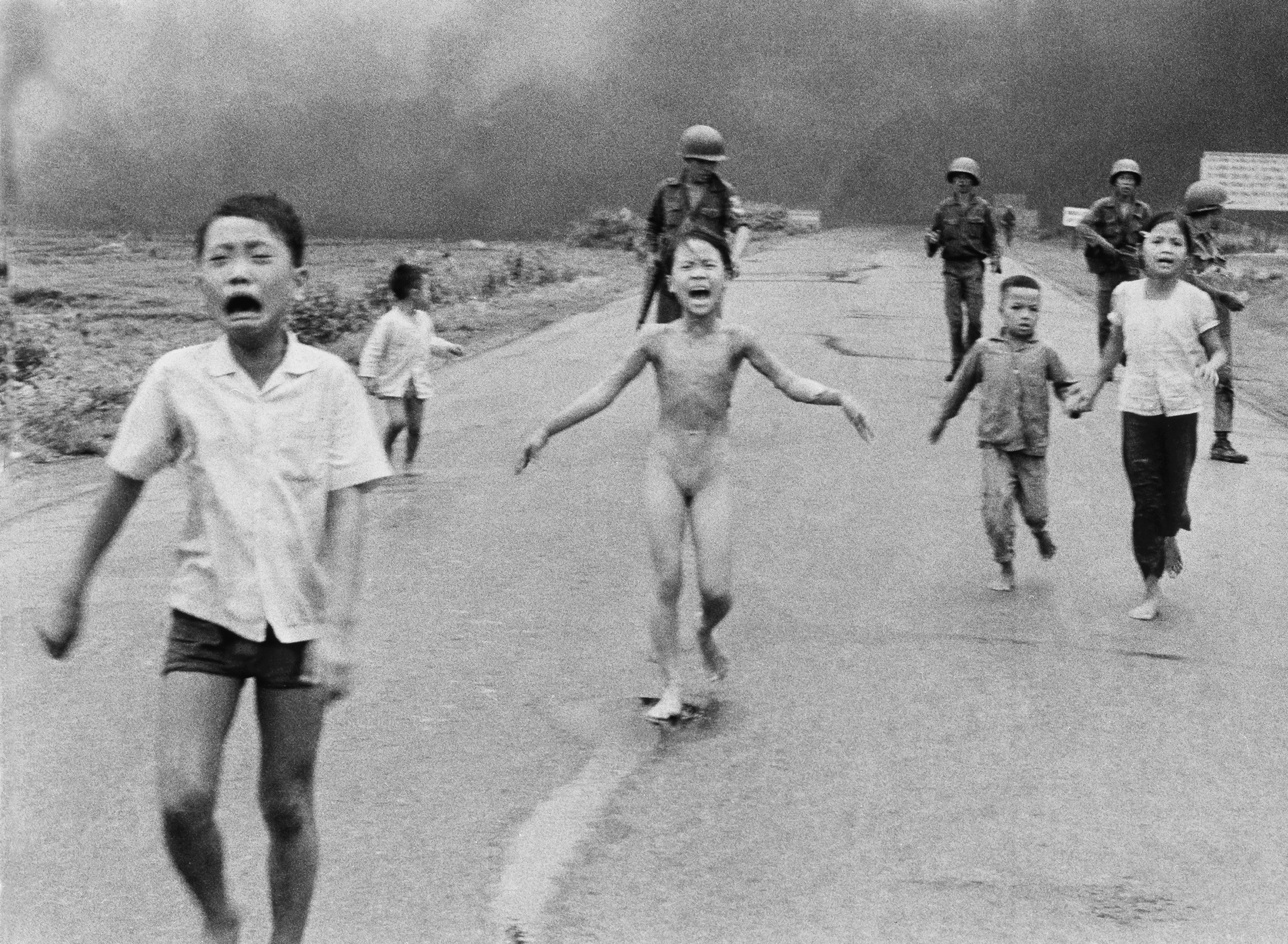 Kim Phuc, as a child, runs down the road, her skin burning with napalm.