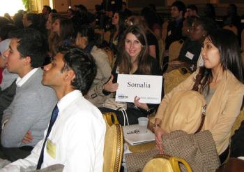 "student in crowd at model un conference holding up paper with ""somolia"" written on it and giving thumns up"