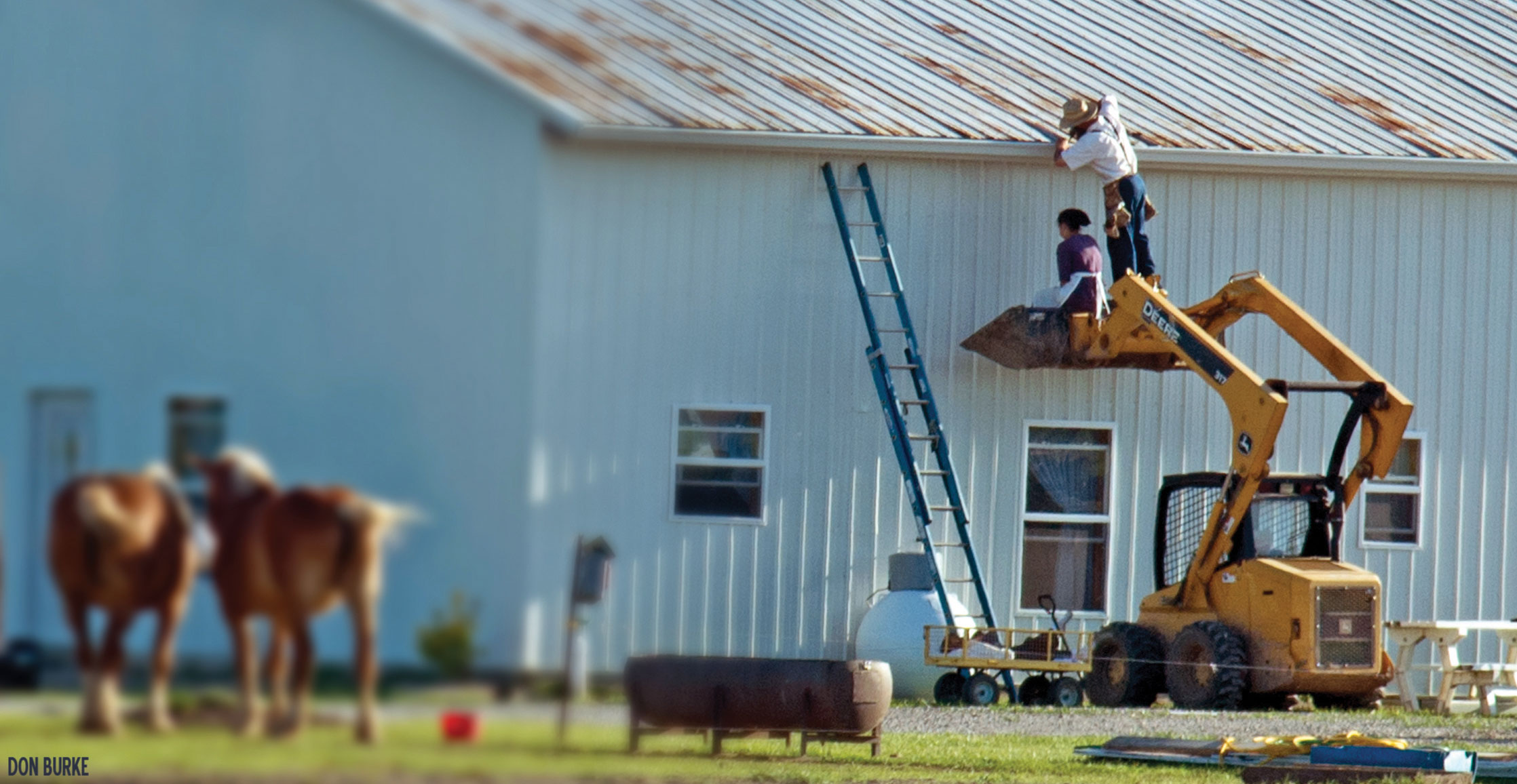 Amish man and woman fixing roof