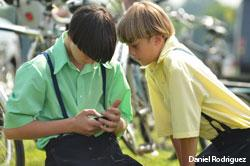 Two Amish boys texting on a cell phone
