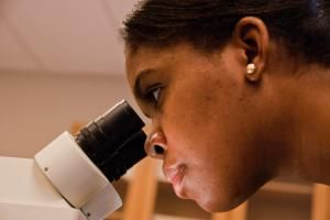 young girl looking into microscope