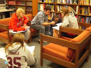 students sitting on couches and floor working in chemistry library surrounded by books