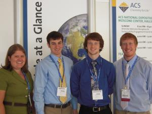 four chemistry students with name badges in front of poster at san francisco conference