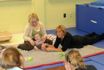 kid zone professor and students with babies on mat