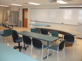 occupations lab classroom with desks, white board and bathroom lab in corner