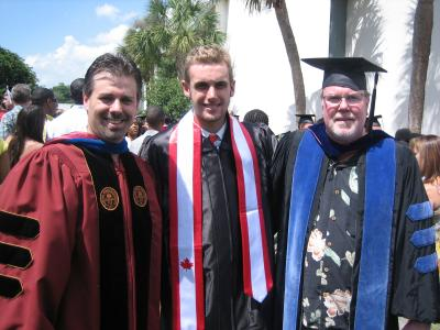 psychology alumni patrick smith with two others at a graduation