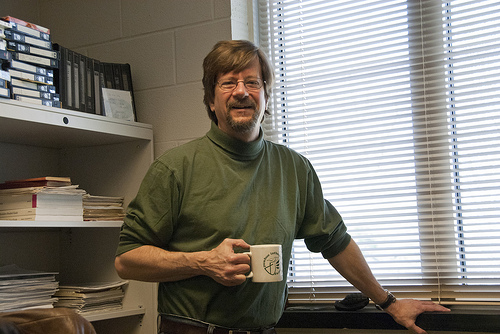 dr john teske holding coffee in front of bookshelf