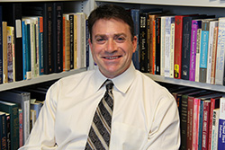 dr t evan smith in front of his bookshelves