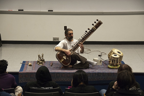 man playing sitar on blanket with drums and gold artifacts on lecture hall stage