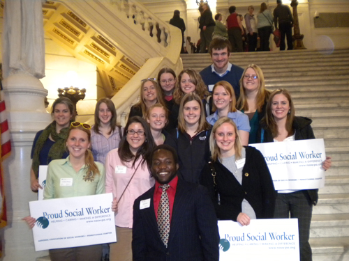 group of social work students on steps inside capitol holding proud social worker signs