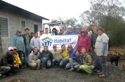 students and faculty group picture in front of habitat for humanity sign on trip to hondorous with