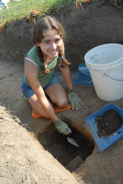 female sociology-antrhopology major in hole during archaeological dig