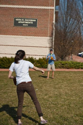 male and female students playing catch in front of hackman apartments