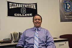 chris mowl at desk with e-town college banner in back