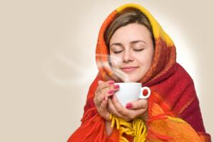 girl wrapped in blanket holding steaming tea cup