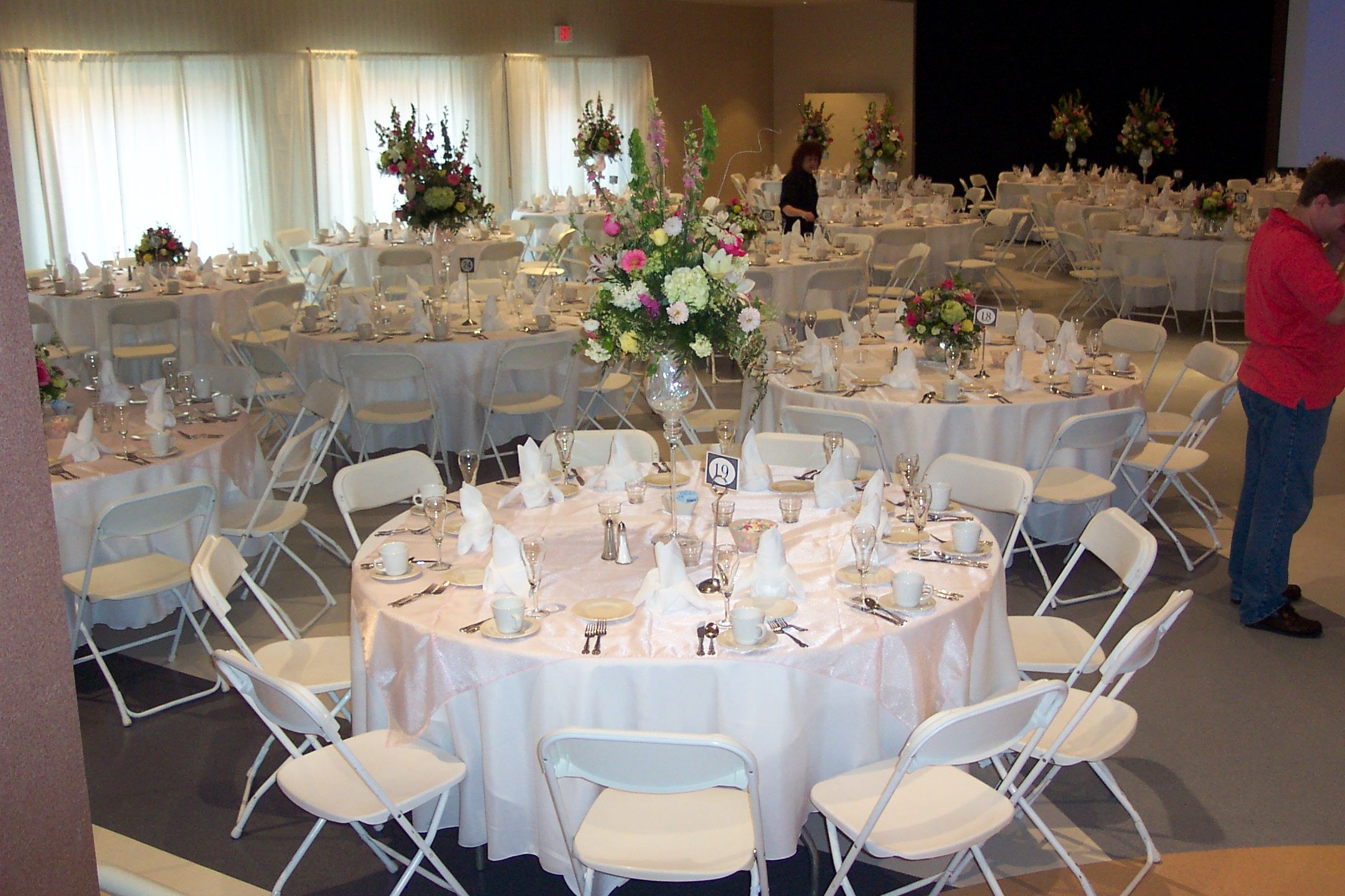 tables set for wedding reception with linens and floral arrangements
