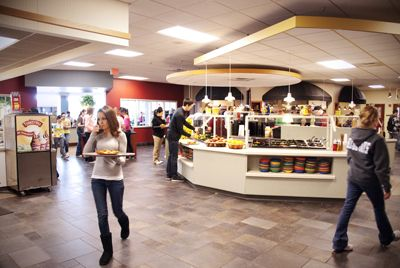 inside of the marketplace at elizabethtown college showing salad bar and students with trays