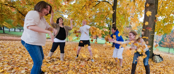 students in dell in fall having a leaf fight