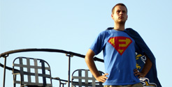 tyler kunkle in e-town superman spoof shirt using e-town blue jays flag as cape