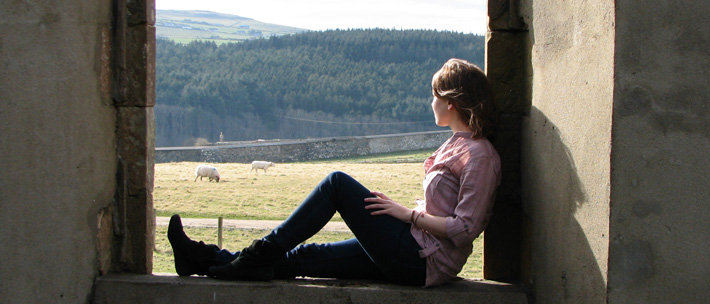 student on stone porch with large columns looking out into Ireland countryside