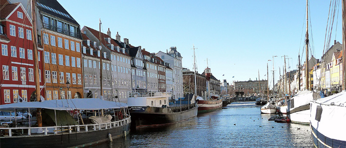 canal in copenhagen with colorful houses and boats along each side